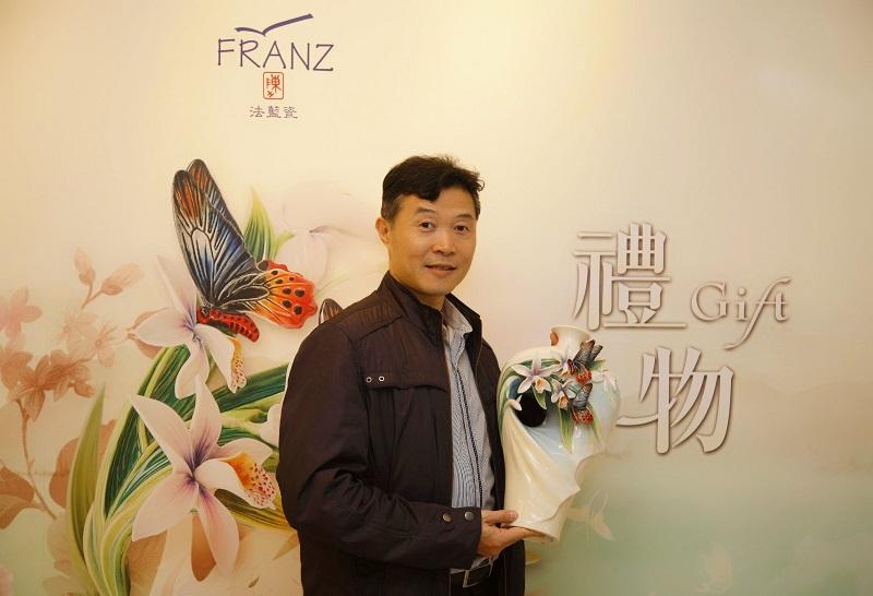 法藍瓷設計師何振武與「花現幸福」瓷瓶合影