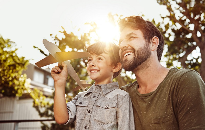 Shot of a happy little boy and his father playing with a cardboard plane in their backyard at home